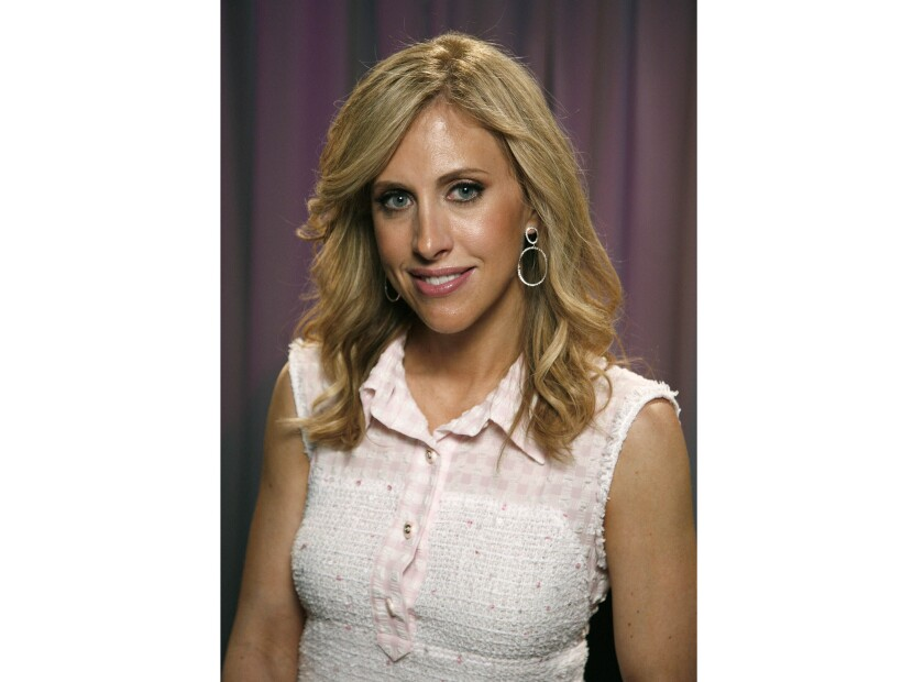 """FILE - This April 28, 2011 file photo shows author Emily Giffin posing for a portrait in New York. Giffin's latest novel, """"The Lies that Bind"""" was released on June 2, 2020. (AP Photo/Jeff Christensen, File)"""