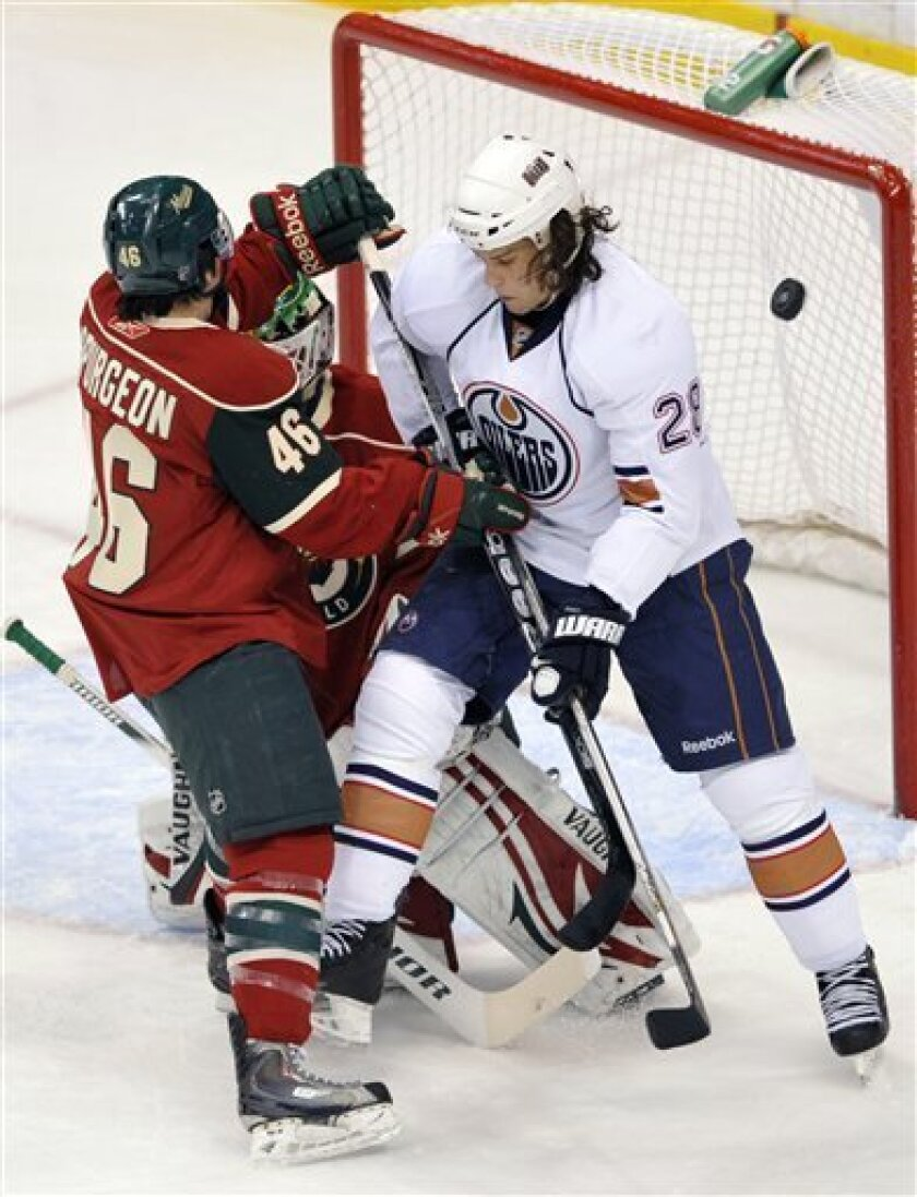 Minnesota Wild's Jared Spurgeon, left, helps goalie Niklas Backstrom (partially obscured), of Finland, defend the net against  Edmonton Oilers' Ryan Jones, right, as a shot goes high over the net during the first period of an NHL hockey game on Thursday, March 31, 2011, in St Paul, Minn. (AP Photo/