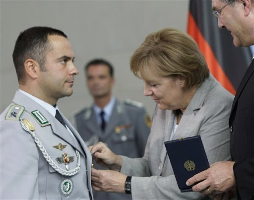 German Chancellor Angela Merkel, center, and Defense Minister Franz Josef Jung, right, present Bundeswehr Master Sgt. Alexander Dietzen, left, with the Cross of Honor for Bravery in Berlin, Germany, Monday, July 6, 2009. Chancellor Angela Merkel was presenting four German soldiers with the new decoration for bravery on Monday, the nation's first such honor since World War II. (AP Photo/Herbert Knosowski)