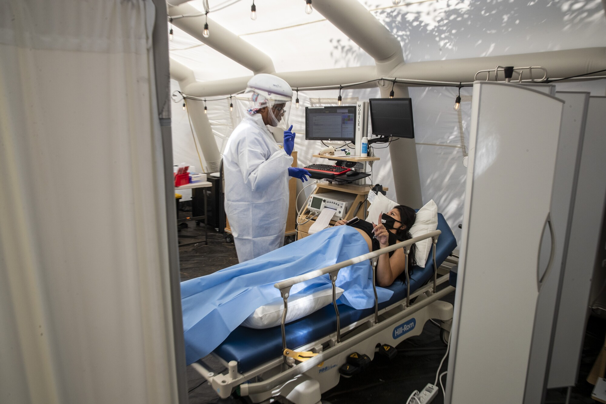 A nurse in PPE screens a pregnant patient in the OB triage tent at Providence Holy Cross Medical Center