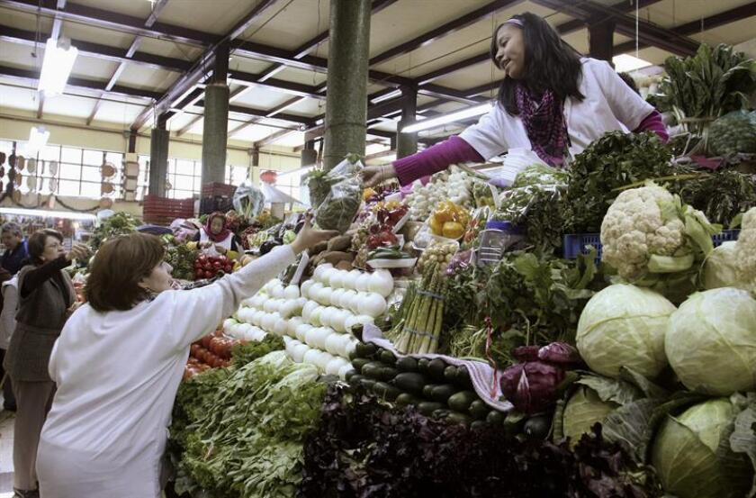 Una mujer compra varios productos en un mercado en Ciudad de México. EFE/Archivo