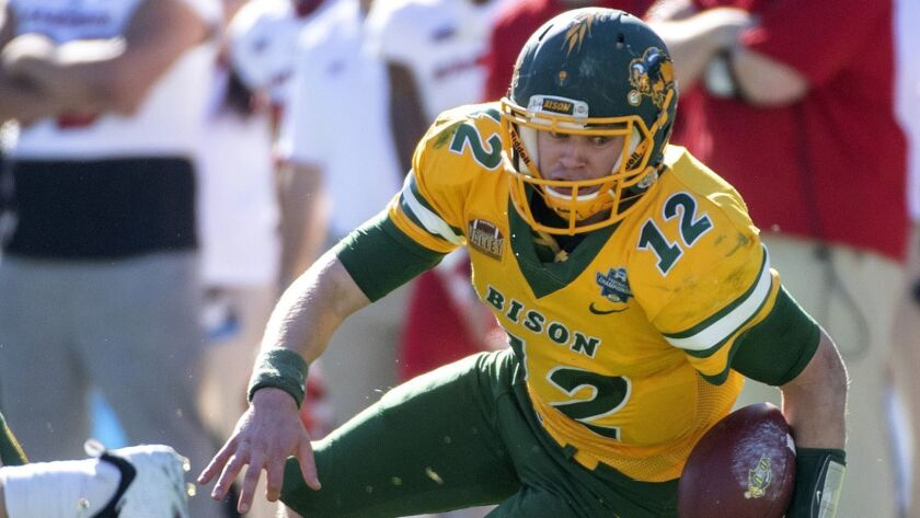 North Dakota State quarterback Easton Stick (12) reaches for extra yardage as he is brought down by