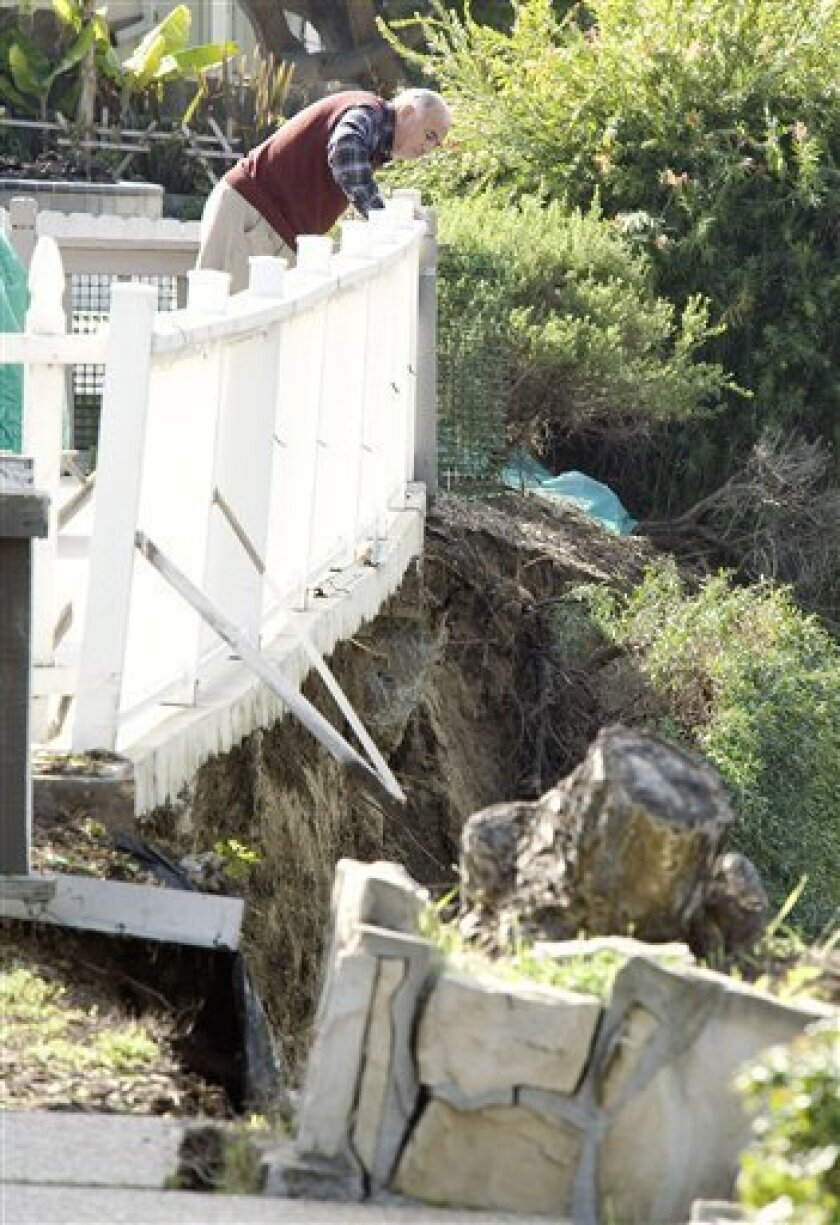 A resident of Via Ballena in San Clemente, Calif., surveys the land that was once his back yard overlooking the Shorecliffs Golf Club Friday, Jan. 7, 2011, after a landslide dropped the property 25 to 50 feet into a ravine below. (AP Photo/Orange County Register, Ken Steinhardt) NO SALES; MAGS OUT; LOS ANGELES TIMES OUT