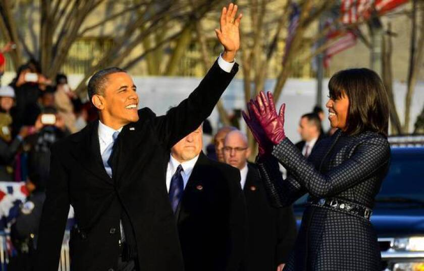 President Obama and First Lady Michelle Obama walk along the inauguration parade route.