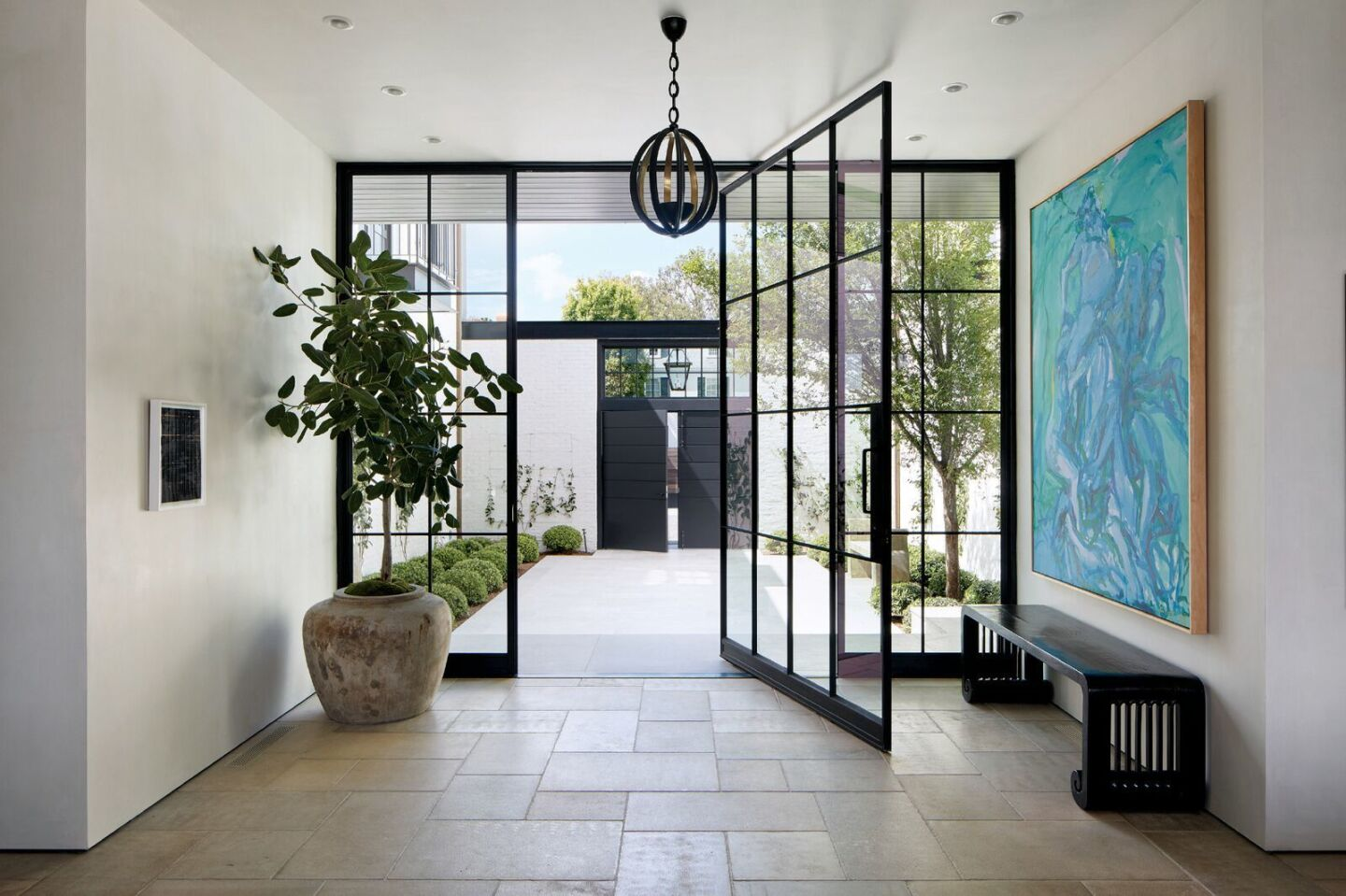 A pivoting steel-and-glass front door opens to the entrance hall, where an artwork by Elaine de Kooning hangs above a vintage bench by Charles Jacobsen. Stone flooring from Exquisite Surfaces; Herve Van der Straeten pendant from Ralph Pucci.
