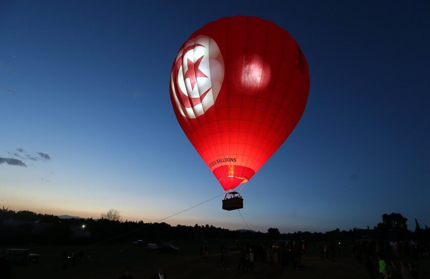 A hot air balloon floats above fields during the Tunisian Balloons Festival in Hammamet, Tunisia on March 22.