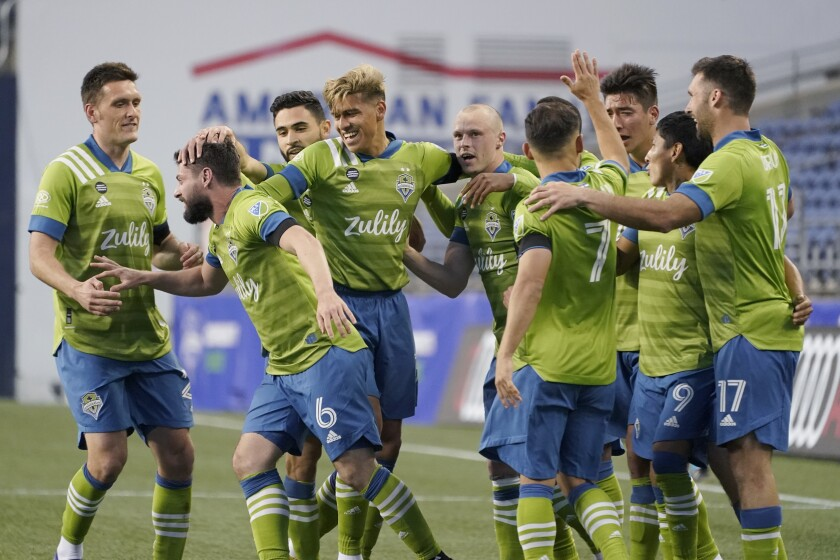 Seattle Sounders midfielder Joao Paulo, second from left, is greeted by teammates after he scored a goal against Minnesota United during the second half of an MLS soccer match, Friday, April 16, 2021, in Seattle. (AP Photo/Ted S. Warren)