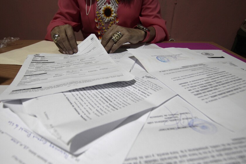 """A Salvadoran businesswoman, who is one of the applicants of a small refugee program that was shut down by President Donald Trump, shows documents of the many times she has reported robberies and extortions, in Santa Ana, El Salvador, Saturday, Aug. 22, 2020. She said she was terrified when she began receiving death threats in 2013. Men with tattoos would come to a car wash she used to own to demand """"monthly compensation"""" for letting her operate. She says she has received many threats since — through calls, text messages and social media. (AP Photo/Salvador Melendez)"""