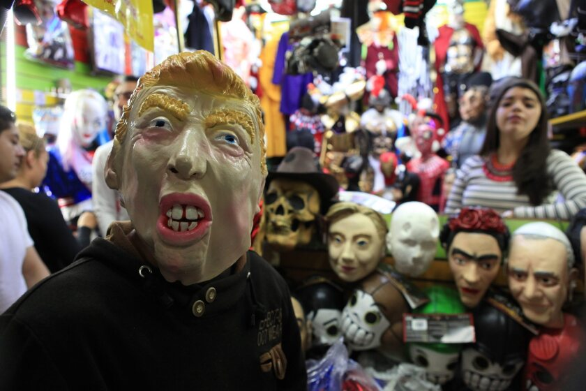 A man tries on a Donald Trump mask at a market in Mexico City on Nov. 6, 2016.