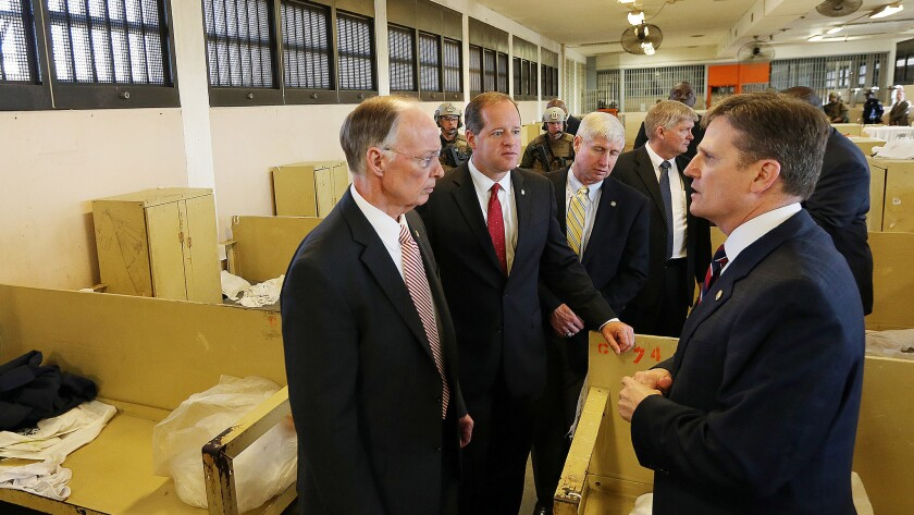 Alabama Gov. Robert J. Bentley, left,  listens to Prison Commissioner Jeff Dunn during a tour of William C. Holman Correctional Facility in Atmore, Ala., in March.