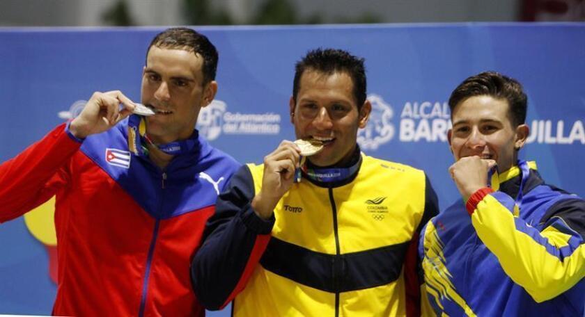El nadador colombiano Omar Pinzon (c), medalla de oro, fue registrado este domingo, junto al cubano Armando Barrera (i), plata, y al venezolano Robinson Molina (d), bronce, durante la premiación de la prueba de los 100 metros dorso masculino de los XXIII Juegos Centroamericanos y del Caribe, en Barranquilla (Colombia). EFE/Luis Eduardo Noriega A.