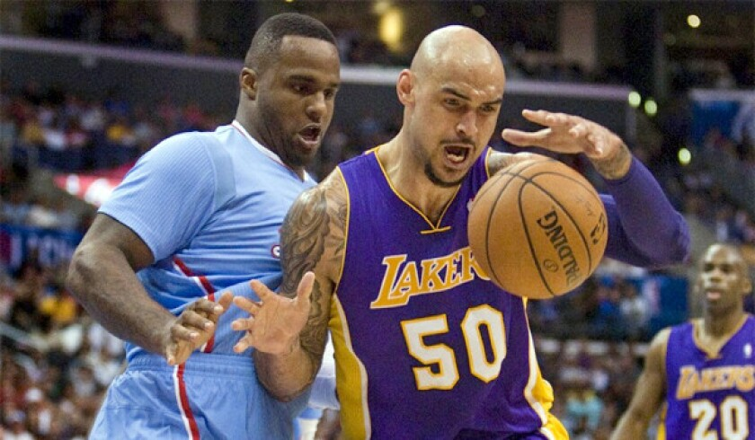 Likely Lakers summer league player Robert Sacre, right, boxes out Glen Davis in a regular-season game against the Clippers on April 6.
