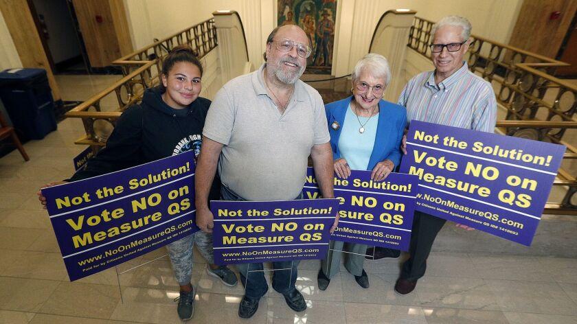 Lauren Applebaum, 16, Larry Applebaum, Audrey Hanson, and Bill Abbey hold No on Measure QS signs out
