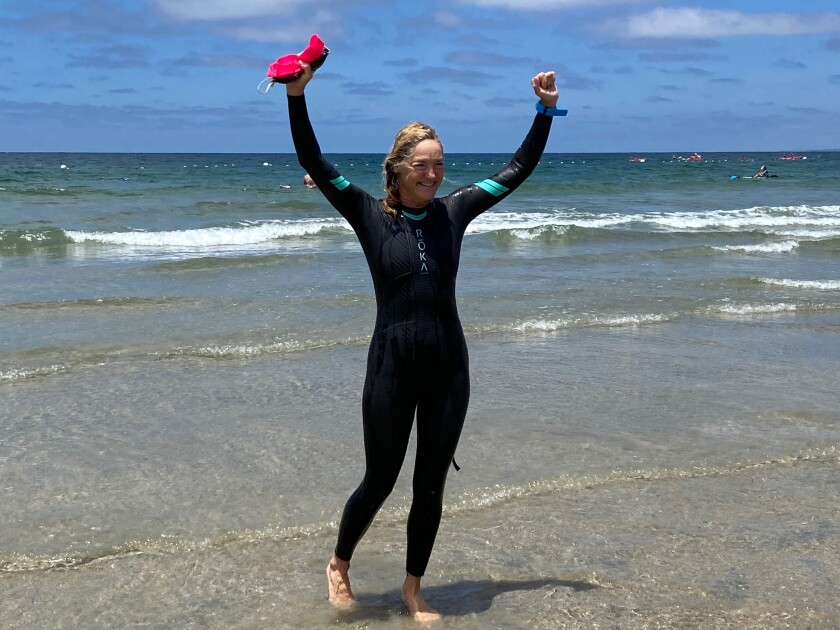 La Jolla resident Laura McDonald emerges from the ocean at La Jolla Shores, having completed a 4-mile swim from Windansea.