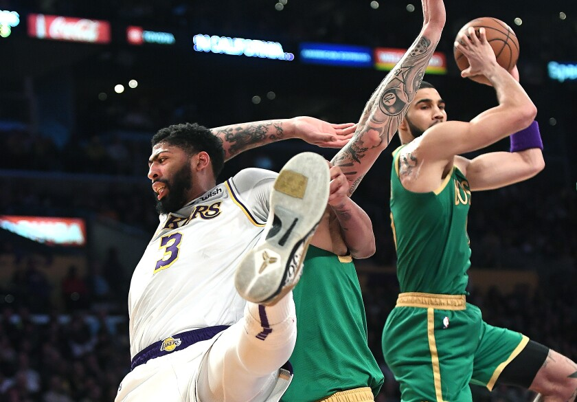 Lakers star Anthony Davis, left, battles with Celtics center Daniel Theis, center, as Jayson Tatum grabs the rebound during Sunday's game at Staples Center.