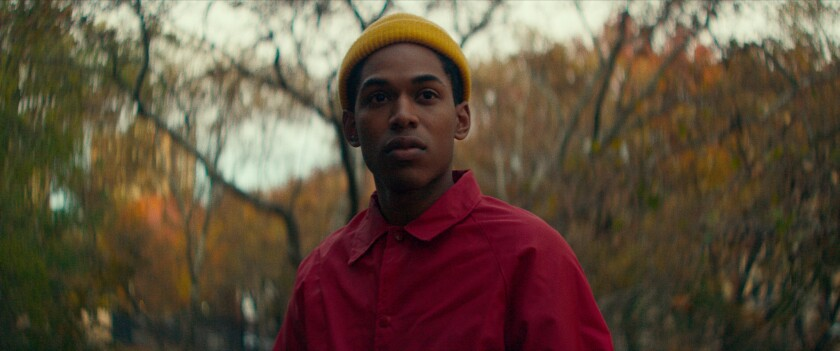 Kelvin Harrison Jr., in a yellow beanie and red shirt, stands in front of trees and fall foliage.