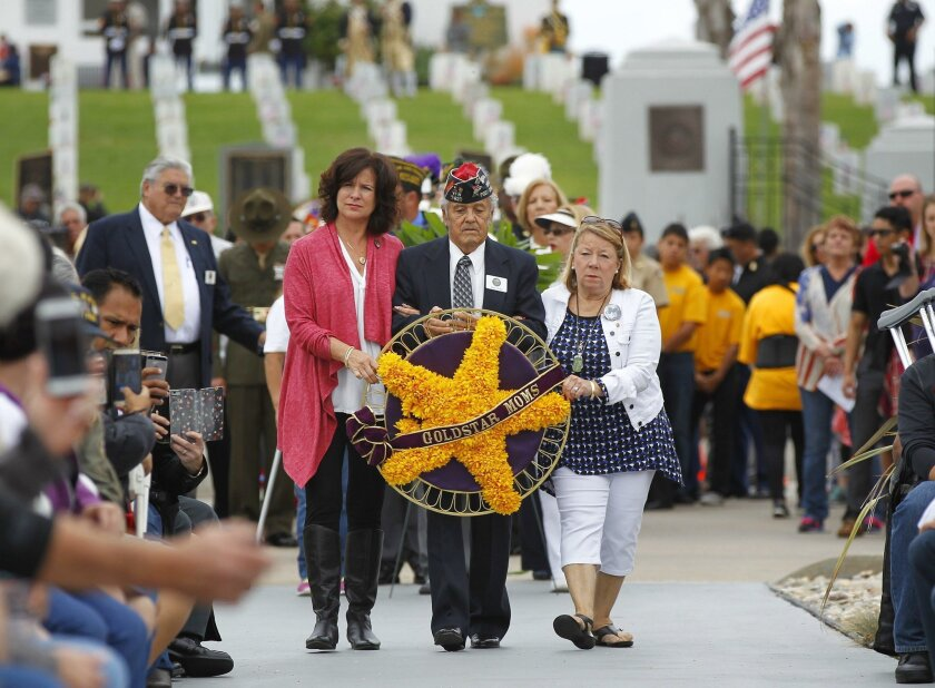 Jill Millard, left, mother of Army Spc. Gregory Millard, and Penny Bento, mother of Army Cpl. Anthony K. Bento carry a wreath during the 116th Memorial Day Service at Fort Rosecrans National Cemetery. Both soldiers from San Diego were killed in 2007 serving suring Operation Iraqi Freedom.