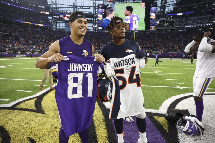 Minnesota Vikings wide receiver Bisi Johnson, left, and Denver Broncos linebacker Josh Watson pose after swapping jerseys.