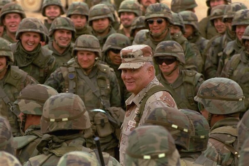 Gen. Norman Schwarzkopf, 6 feet 3 and 230 pounds, stands out among soldiers of the 1st Infantry Division during a visit to the troops in the Saudi Arabian desert.