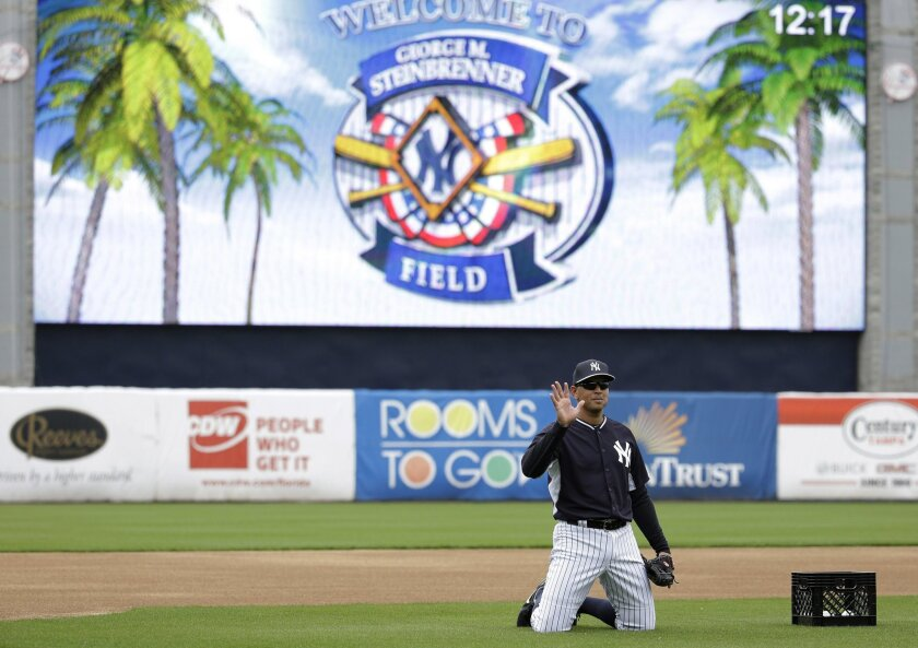 New York Yankees' Alex Rodriguez waves as he does drills at third base during a spring training baseball workout, Thursday, Feb. 26, 2015, in Tampa, Fla. (AP Photo/Lynne Sladky)