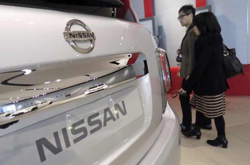 Visitors walk past a Nissan car at its global headquarters in Yokohama, near Tokyo, Wednesday, Feb. 10, 2016. Japanese automaker Nissan Motor Co. says its fiscal third quarter profit grew 25 percent to 127.2 billion yen ($1.1 billion) on strong sales. (AP Photo/Eugene Hoshiko)