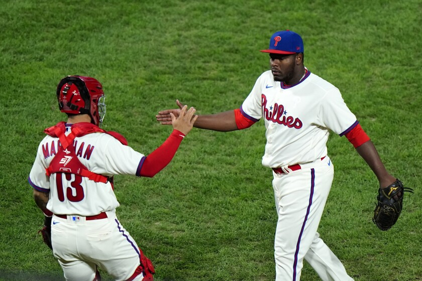 Philadelphia Phillies pitcher Hector Neris, right, and catcher Rafael Marchan celebrate after winning the second baseball game in a doubleheader against the Toronto Blue Jays, Friday, Sept. 18, 2020, in Philadelphia. (AP Photo/Matt Slocum)