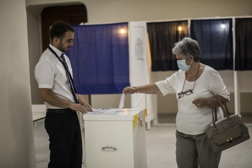 Una mujer deposita su boleta en un centro de votación durante un referéndum sobre el aborto en Gibraltar, el 24 de junio de 2021. (AP Foto/Javier Fergó)