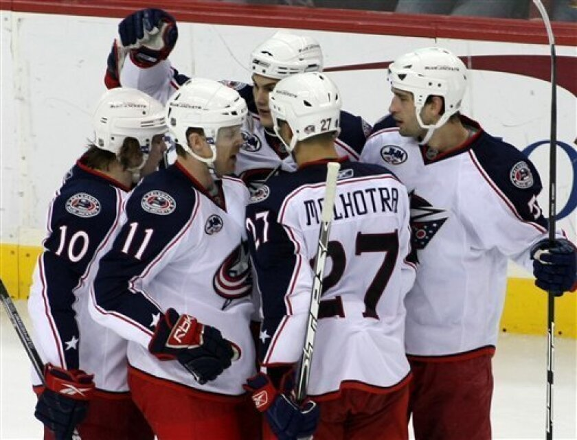 Columbus Blue Jackets' Craig MacDonald (11) celebrates with teammates Kris Russell (10), Jared Boll, top left background, Fedor Tyutin, top right, of Russia, and Manny Malhotra (27) after scoring a goal against Washington Capitals goalie Jose Theodore during the second period of an NHL Hockey game