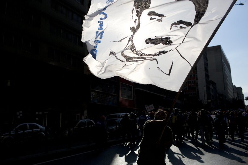 A demonstrator waves a flag with the image of Venezuelan President Nicolas Maduro at a rally in support of the government in Caracas on Tuesday.