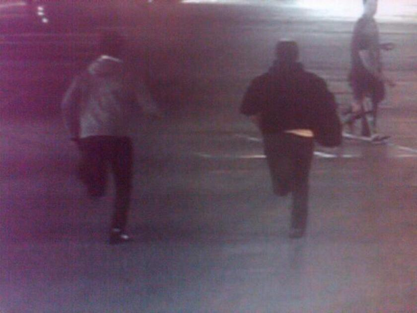 Two suspects in the stun gun robbery of a security guard from an armored truck are seen running from the scene of the crime on surveillance camera footage at the Fashion Valley Mall in San Diego.