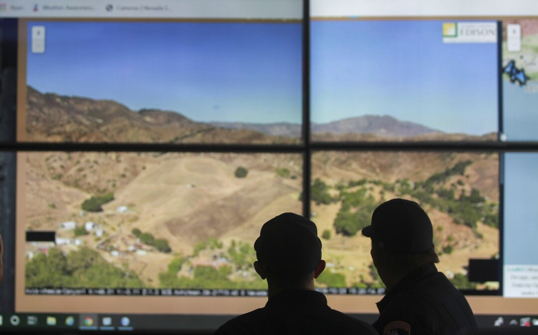 Cal Fire captains Kevin Cox, right, and Ryan Silva look at a screen as they demonstrate the use of wildfire surveillance cameras, mounted on various mountain tops in San Diego County, while in the Cal Fire emergency command center at the Cal Fire San Diego Unit Headquarters on Wednesday, October 23, 2019 in El Cajon, California.