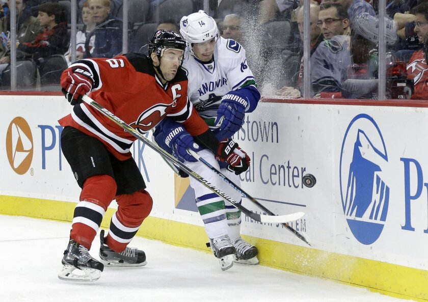 Vancouver Canucks right winger Alexandre Burrows (14) and  New Jersey Devils defenseman Andy Greene (6) collide as they chase the puck during the first period of an NHL hockey game, Sunday, Nov. 8, 2015, Newark, N.J. (AP Photo/Mel Evans)