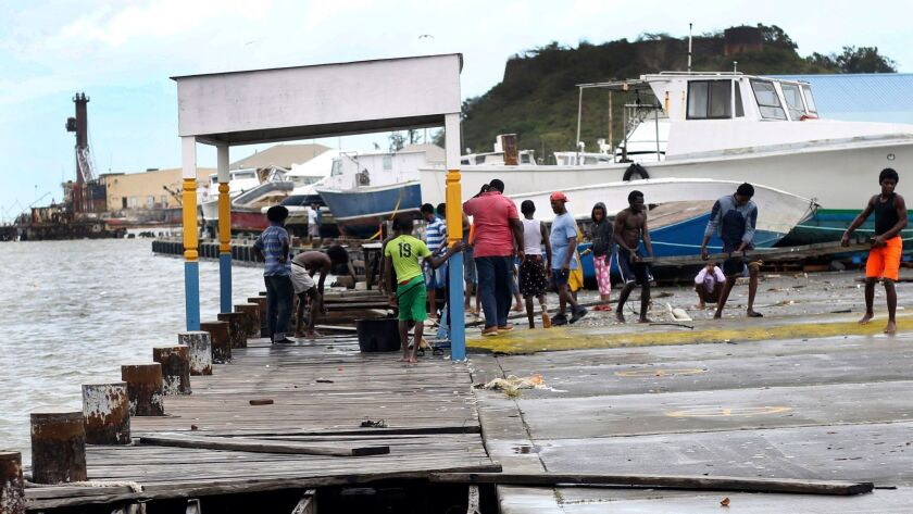 Debris is cleared from a damaged dock in St. John's, Antigua and Barbuda, after Hurricane Irma roare