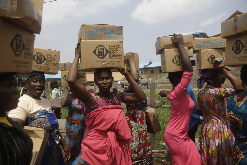 Residents of Oworonshoki Slum carry their food parcels distributed by the Lagos Food Bank Initiative, a non-profit nutrition focused initiative committed to fighting hunger and solving problems of Malnutrition for poor communities , in Lagos, Nigeria, Saturday, July 10, 2021. (AP Photo/Sunday Alamba)