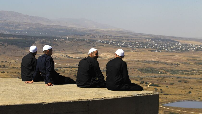 Druze men at the Israeli-annexed Golan Heights look out across the southwestern Syrian province of Quneitra, visible across the border, on July 7, 2018.