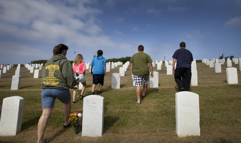 Sally Gannon and her 4 children walk up to her husband Rick's graveside at Fort Rosecrans National Cemetery.