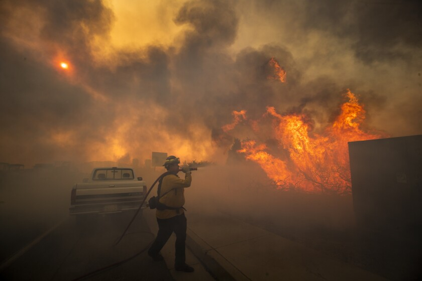 Firefighter Raymond Vasquez fights the Silverado fire fueled by Santa Ana winds at the 241 toll road