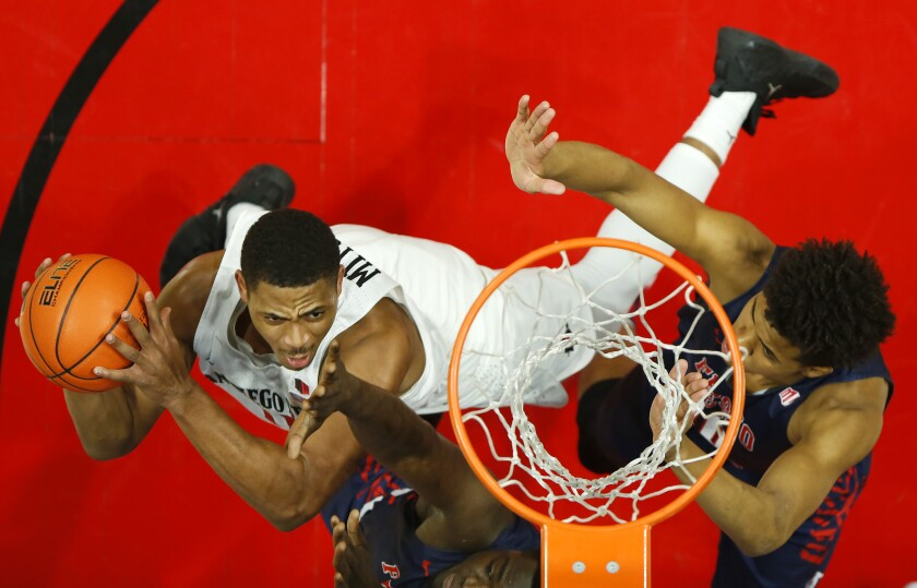 San Diego State's Matt Mitchell, left, goes up for a shot against Fresno State defenders on Jan. 1, 2020.