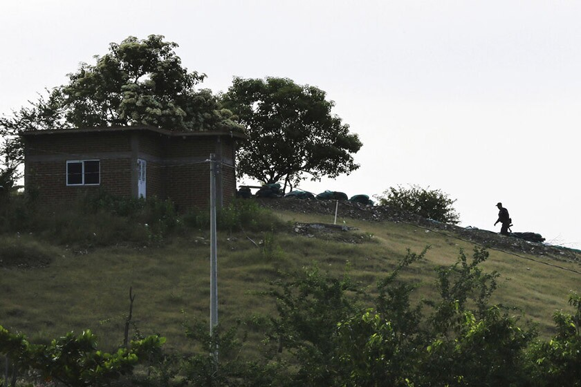 A heavily armed vigilante heads to a sniper post atop a hill on the outskirts of Tepalcatepec, Mexico. The vigilantes guard against incursions by the Jalisco cartel.