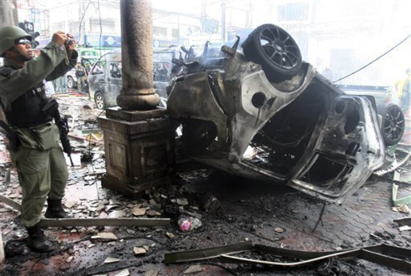 A Thai soldier takes photograph of wreckage of cars after the car bomb attack in Yala province, Southern Thailand Saturday, March 31, 2012. Suspected Muslim insurgents set off coordinated bomb blasts as shoppers gathered for lunch Saturday in a busy hub of Thailand's restive south, killing eight people and wounding more than 60, officials said. (AP Photo/Sumeth Panpetch)