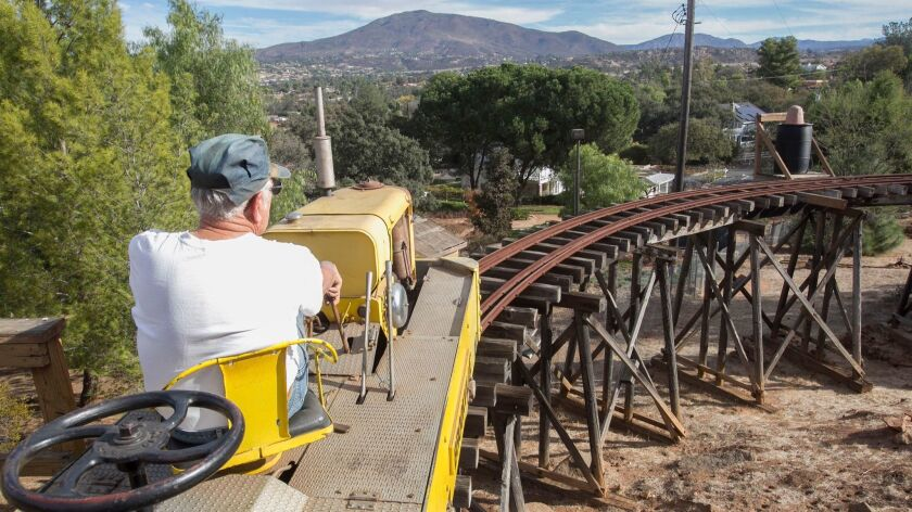 Roy Athey, owner of the Descanso, Alpine and Pacific Railway in Alpine, steers his little engine and one car over the trestle that he built on his property.