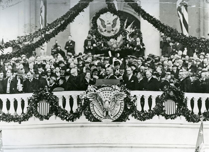 FDR is sworn in by Chief Justice Charles Evans Hughes on March 4, 1933. Seen at FDR's back, looking downcast: Herbert Hoover.