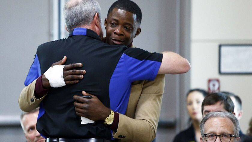 James Shaw, right, gets a hug from Waffle House CEO Walt Ehmer during a press conference on the Waff