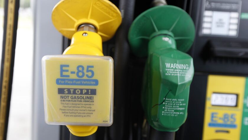 FILE - In this Aug. 9, 2014 file photo, a fuel nozzle for E-85, left, and traditional gasoline is se