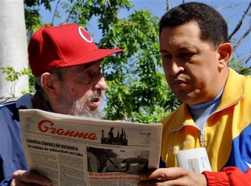 In this photo released by Granma newspaper, Cuba's Fidel Castro, left, and Venezuela's President Hugo Chavez look at Granma state newspaper in an unknown location in Havana, Cuba, Tuesday June 28, 2011. Chavez underwent surgery in Cuba two weeks ago and has been unusually quiet since then. Allies o