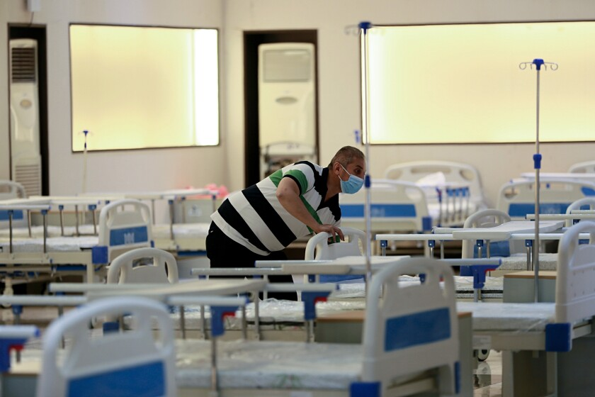 In this Saturday, June 20, 2020 photo, workers set up a field hospital to treat patients with COVID-19 in Baghdad, Iraq. New field hospitals have been erected to treat virus patients as hospitals reach capacity, but health workers fear the worst is still to come. (AP Photo/Hadi Mizban)