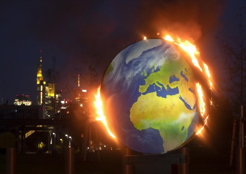 Una maqueta del planeta Tierra arde ante la sede del Banco Central Europeo en Fráncfort, Alemania.