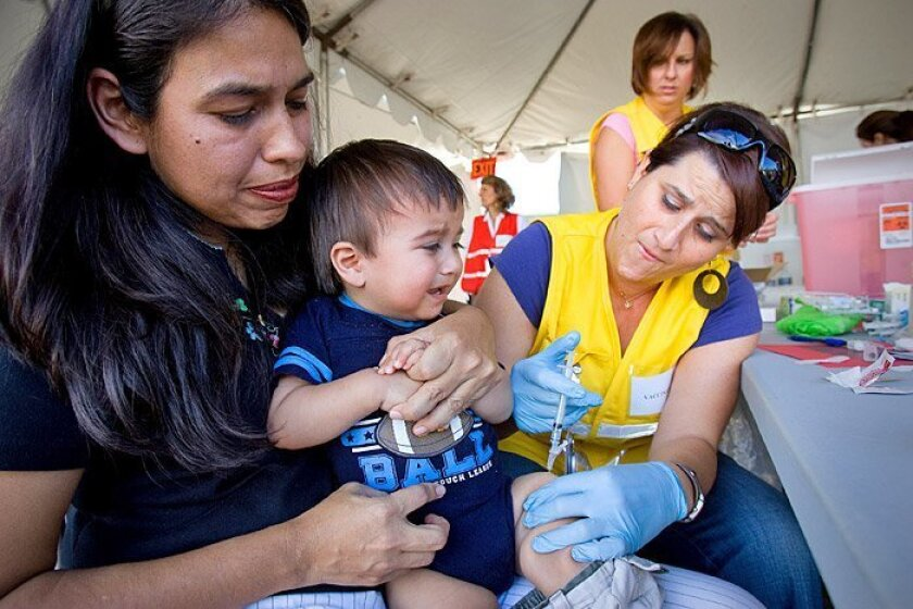 Blanca Juarez held her 1-year-old baby, Gambino, as he received the H1N1 vaccine from Jenny Cortez, a nurse at Rady Children's Hospital. County providers now have received more than 1.2 million doses.