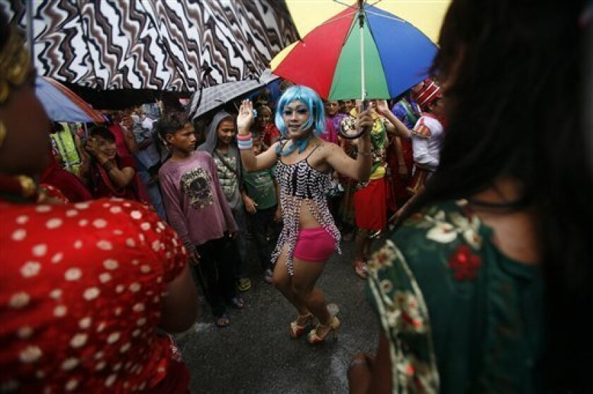 Gays, lesbians, transvestites and their supporters dance as they participate in a gay rally in Pokhara 200 kilometers (125 miles) from Katmandu, Nepal, Friday, Aug. 3, 2012. Hundreds of gay, lesbian and transgender people marched in a Nepal town to demand recognition as a third gender in citizen certificates, to allow same-sex marriage and support criminalizing discrimination based on sexual preference. (AP Photo/Niranjan Shrestha)