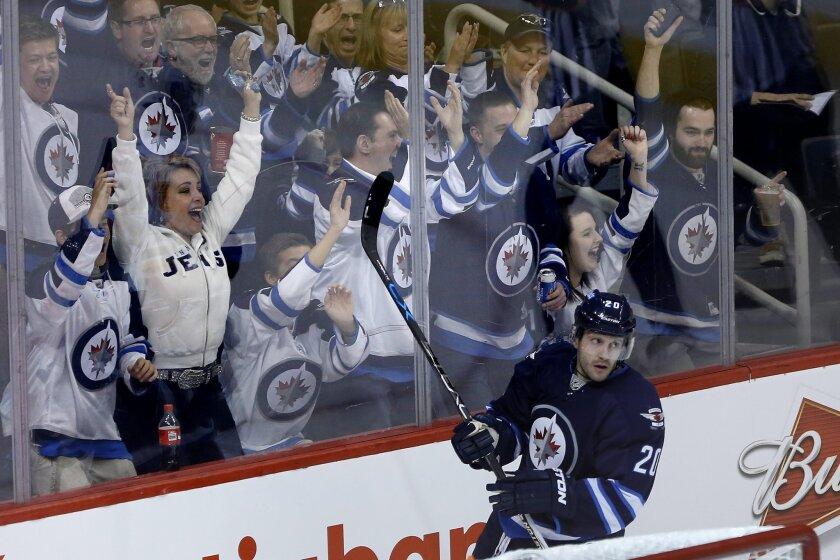 Winnipeg Jets' Lee Stempniak (20) and fans celebrate his goal against the Calgary Flames during the third period of an NHL hockey game, Saturday, April 11, 2015 in Winnipeg, Manitoba. (John Woods/The Canadian Press via AP) MANDATORY CREDIT
